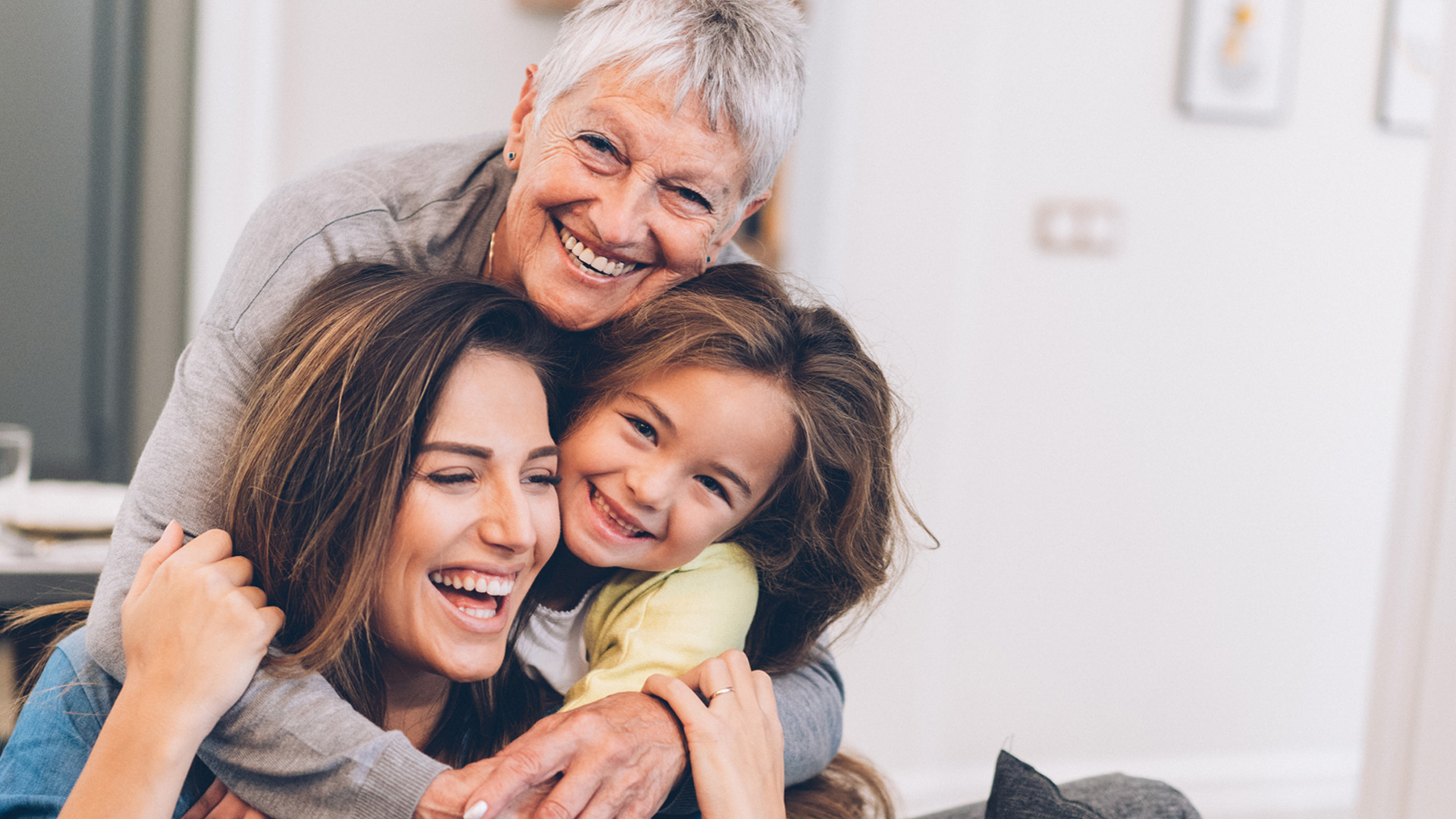 Three generations of women hugging each other.