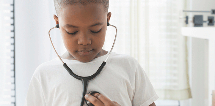 A young boy listening to his heartbeat with a stethoscope.
