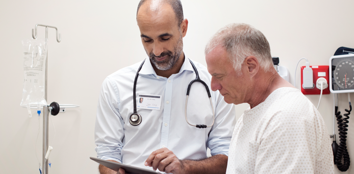 A doctor reviewing a document with his patient.