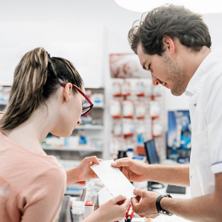 A woman and a pharmacist looking at a receipt.